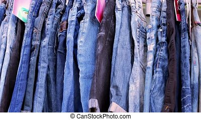 Close up of many blue jeans hanging on a rail. Video macro...