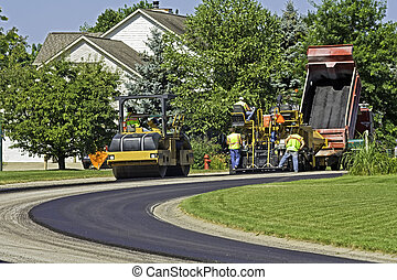 Laying new pavement in a residential neighborhood -...