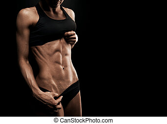 Beautiful athletic woman shakes her abdominal muscles on...