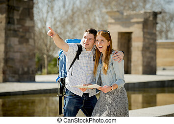 American student and tourist couple reading city map in...