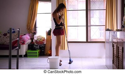 Beautiful young sexy maid cleans tiled floor, concept...