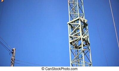 View of tower crane on a background Of blue sky. Video shift...