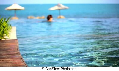 Woman swimming in pool and ocean at the background. Video...