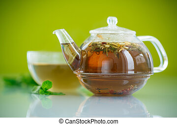 green tea in a glass pot on a green background