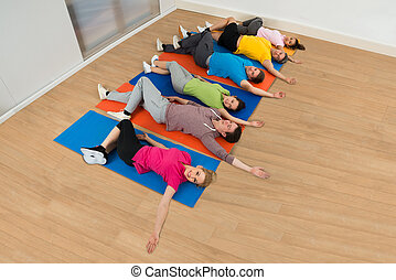 Multiethnic Group Of Happy People Exercising On Mat At Gym