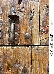 Latch - Forefront of the handle of a wooden door.