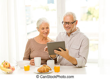 happy senior couple with tablet pc at home