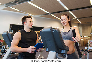 woman with trainer exercising on stepper in gym - sport,...