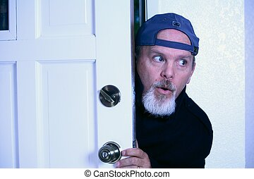 Man sneaking into house from doorway. - Man sneaking into...