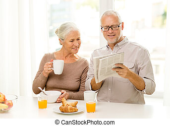 happy senior couple having breakfast at home - family,...