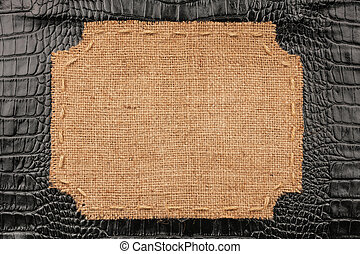 Frame of burlap, lies on a background of crocodile leather,...