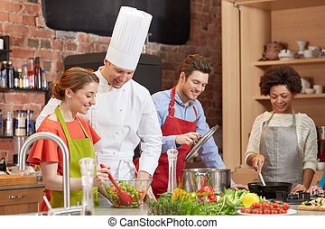 happy friends and chef cook cooking in kitchen - cooking...