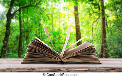 Open book  on wood table in green forest