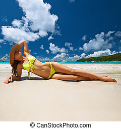 Woman in yellow bikini lying on beach at Seychelles - Woman...