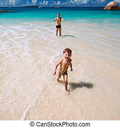Father and two year old boy playing on beach - Two year old...
