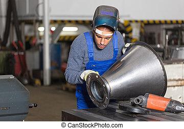 Welder inspecting metal piece for quality control - Welder...