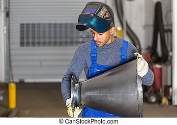 Welder inspecting metal piece for quality control - Welder...