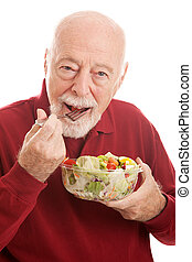 Healthy Salad For Fit Senior - Fit senior man eating a...