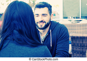young couple relaxing together in street cafe