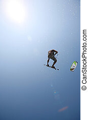 kite surfer - Kite surfer jumping towards the sun with water...