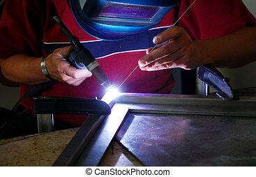 welder welding a metal piece in the factory