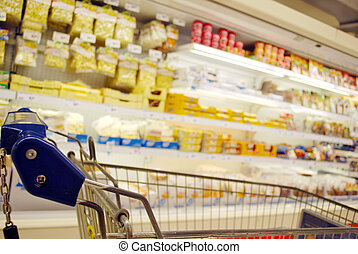 blurred supermarket shelves with focus on shopping cart