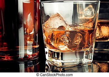whiskey with ice in glass on black background near bottle,...