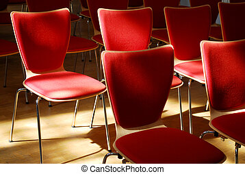 many red chairs standing in row with light and shadow