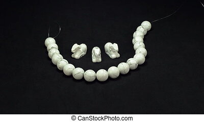 White howlite items on black - Womanu2019s hands are putting...