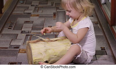 Girl playing with log - Little girl wearing big slippers mom