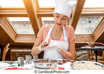 Woman making handmade candy - Young smiling woman chef...