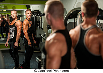 Twin brothers looking in mirror after body building workout...