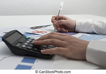 Young businesswoman calculating financial documents - Photo...