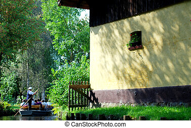 "captain on ""spreewald\"" boat on creek with tourists"