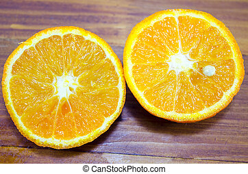 Halved orange on a wooden table close up - Two halves of...