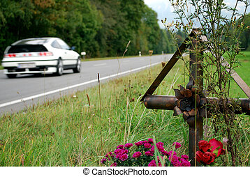 cross with flowers on the edge of a country road for...