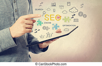 Young man pointing at SEO concept over a tablet