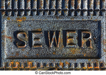 Sewer access cover with rusty iron - A sewer access cover...