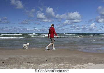 Woman Walking on a Lake Huron Beach with a Small White Dog -...