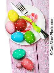 colorful easter eggs and cutlery isolated on white