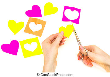 Female hands cut out paper hearts for Valentines Day