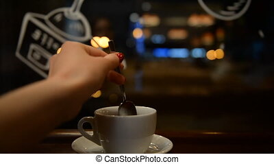 Young girl drinking tea in a cafe in the evening