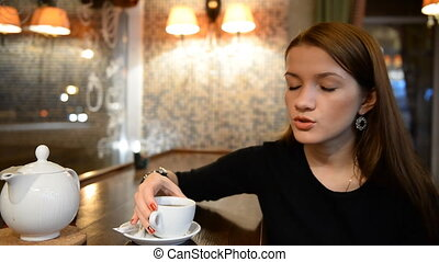 Young girl talking with someone in an evening bar,...
