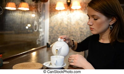 Young girl drinking tea in the evening bar, restaurant, cafe