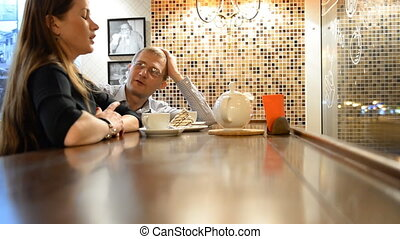 Man and woman talking in the evening bar, restaurant, cafe