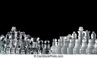 4K. Chess pieces is standing on glass board - Chess pieces...