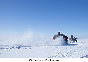 man riding quad bike on snowy winter field - motorcycle with...