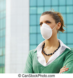pollution - woman standing against office building and...