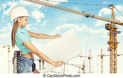 Woman in helmet standing half turn and holding paper sheet...