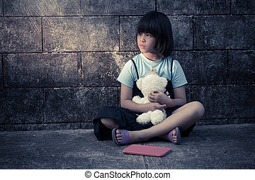 portrait of a sad and lonely Asian girl against grunge wall...